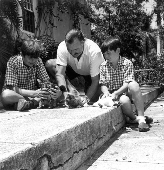 Hemingway with sons Patrick and Gregory with kittens